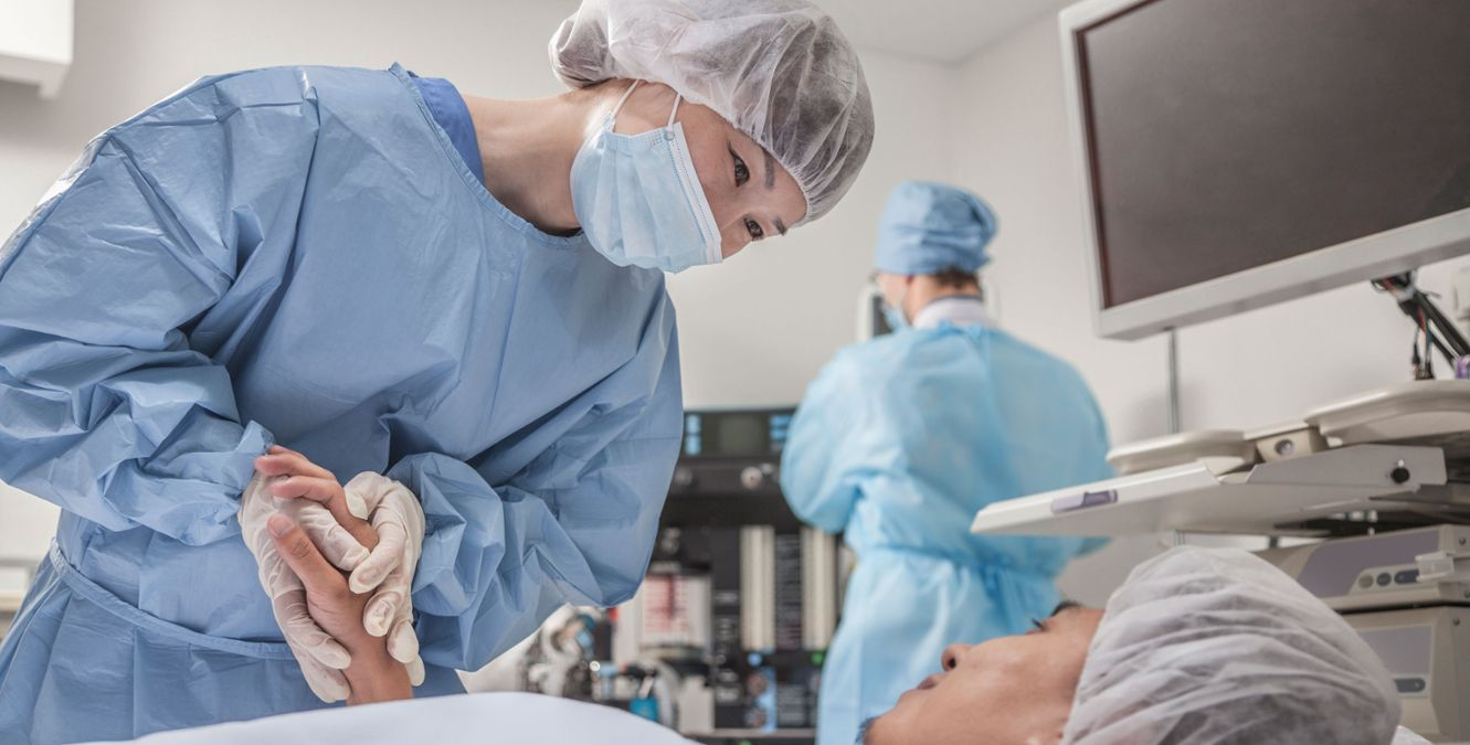 A surgeon is taking care of a patient in the operating theater