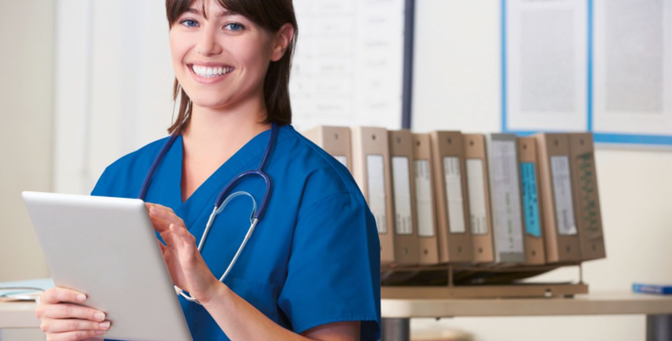 a healthcare professional checks a document while smiling